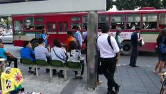 Public autobus departs from bus stop, tracking shot, crowded pedestrian area Stock Footage