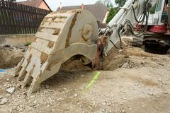 excavator ploughshare on trench - constructing canalization - stock photo