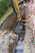 excavator on trench - constructing canalization - stock photo