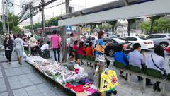 Asian people sit at bus stop shelter, waiting for transport, lively city area Stock Footage