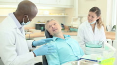 Dentist converses with patient, both smiling and laughing Stock Footage