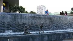 Waterfall decorated with realistic children sculptures, office building basement Stock Footage