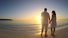 Young Caucasian male female couple on vacation beach at sunrise - stock footage