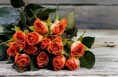Bouquet of yellow-red roses on an old wooden table - stock photo
