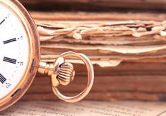 Vintage pocket watch closeup on a background of books - stock photo