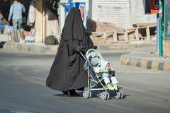 Arabic woman in hijab conducts carriage with child Stock Photos