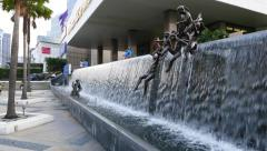 Children jump from waterfall edge, bronze sculptures at sidewalk Stock Footage