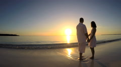 Caucasian couple wearing white clothes barefoot on the beach - stock footage