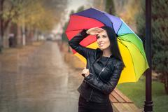 Happy Autumn Woman Holding Rainbow Umbrella Checking for Rain - stock photo