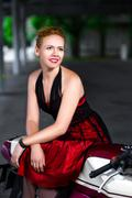 Biker girl in dress on a motorcycle over the background of dark hall Stock Photos