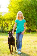 blonde girl walking with the dog or doberman in summer park - stock photo