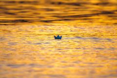Stock Photo of The toy paper boat on the surface water by the bright sunlight backround