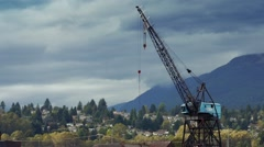 Birds Fly Near Crane Near Mountain Town Stock Footage