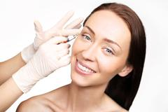 Filling of wrinkles, crow's feet, injection of acid - stock photo