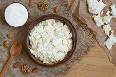 Homemade cottage cheese healthy dairy product with nuts in rustic wooden dish on - stock photo