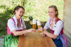Mother and daughter sitting at a table in dirndl in front of a glass of beer. - stock photo