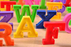 Plastic colorful alphabet letters on a wooden background - stock photo