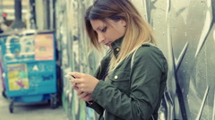 Young lonely woman writing text message on the mobile phone in the city Stock Footage