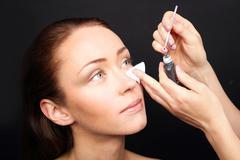 Painting eyelashes, permanent eye makeup - stock photo