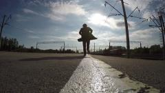 Silhouette of man running on edge of railroad platform - stock footage