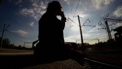 Silhouette of man sitting on railway platform and talking on phone. Stock Footage