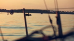 Sunset view from nose of yacht and sun reflected in water like blurred bokeh Stock Footage