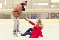 Stock Photo of man helping women to rise up on skating rink