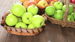 Variety of organic apples in baskets on wood table. Stock Footage