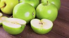 Variety of organic apples sliced on wood table. Stock Footage