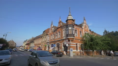 Driving cars on Ilarie Chendi street, near a beautiful building, Sighisoara Stock Footage
