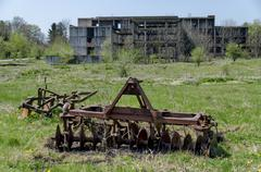 Abandoned unfinished building and farm machinery Stock Photos