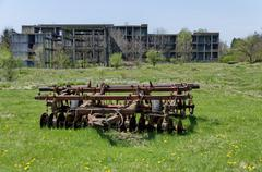 Abandoned unfinished building and farm machinery - stock photo