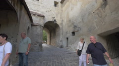 Old people walking on an alley inside the Clock Tower, Sighisoara Stock Footage