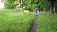 Two boys dressed in white running with his father on a path in a park holding Stock Footage