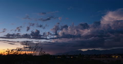 4K Cine 24p dusk stray storm cell heads over mountains colorful time lapse Stock Footage