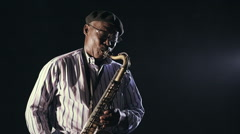 African man colored old black playing saxophone dark background music Stock Footage