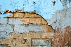 Brick wall with cracks and an old plaster as background Stock Photos
