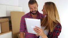 Young couple  choosing furniture to their new apartment using tablet pc. Stock Footage