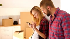 Couple trying to connect mobile phone to the internet in their new apartment. Stock Footage