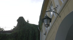 Building with old lamp next to a green wall in Sighisoara Stock Footage