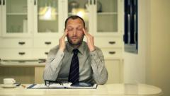 Tired businessman with tablet computer having headache at home at night - stock footage