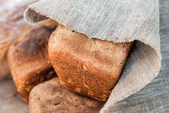 Loaf of rye bread covered with coarse linen cloth Stock Photos