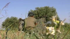 Hunter behind a camouflage net Stock Footage