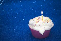 Cupcake with a lit candle over bright blue background - stock photo