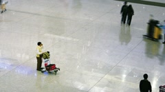Blurred, high speed shot of passengers milling about with carts and luggage Stock Footage