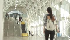 Traveling Girl walks with luggage through bright airport terminal Stock Footage