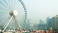 Big ferris wheel and other amusement rides with Hong Kong's smoggy Stock Footage