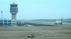 Commercial airliner taxiing past the air traffic control tower Stock Footage