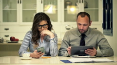 Businesspeople working with smartphone and tablet sitting by table at night Stock Footage