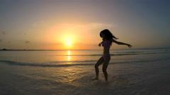 Young ethnic female dancing in bikini on the beach Stock Footage
